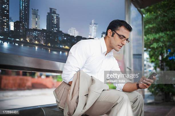 Businessman text messaging on a mobile phone at bus stop