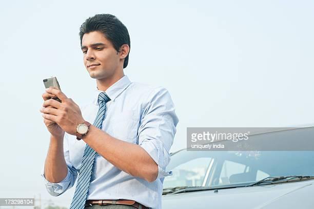 Businessman text messaging on a mobile phone, Gurgaon, Haryana, India