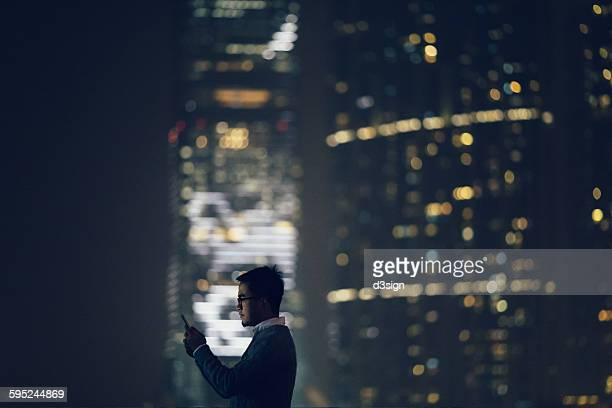 Businessman text messaging on smartphone in city