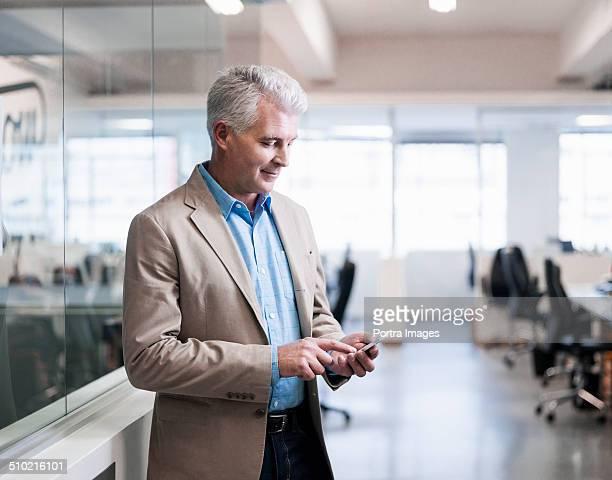 Businessman text messaging through smart phone