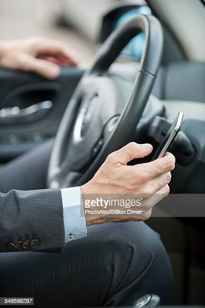 Businessman text messaging while driving, cropped