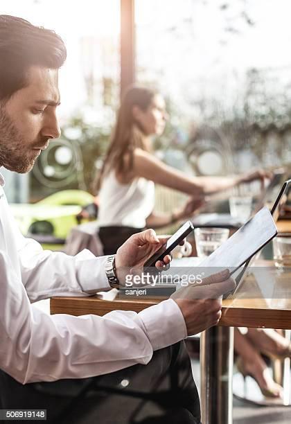 Hombre enviando mensajes de texto en el bar de la cafetería