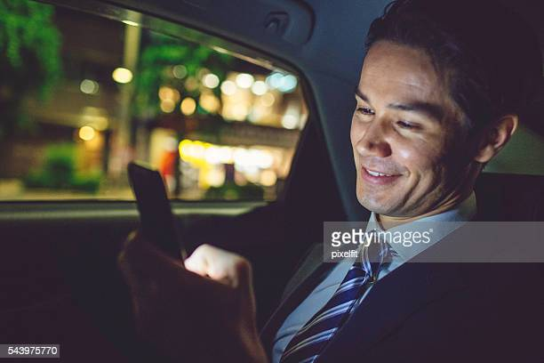 Businessman texting in a car at night