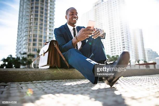 businessman texting in miami sitting on the park