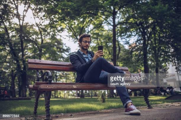 geschäftsmann sms im öffentlichen park - sitzbank stock-fotos und bilder
