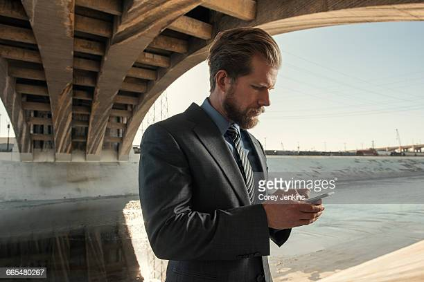 Businessman texting, Los Angeles river, California, USA