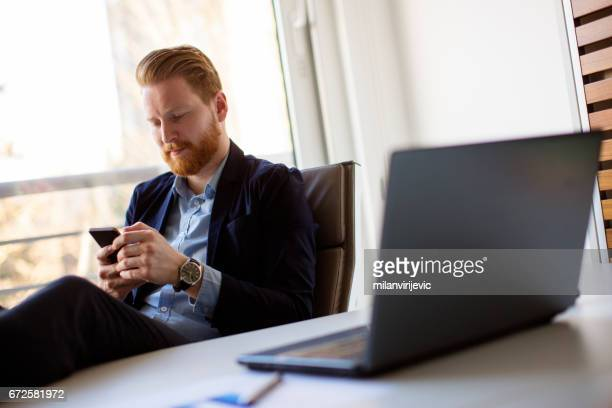 Businessman texting message and sitting at desk with feet up