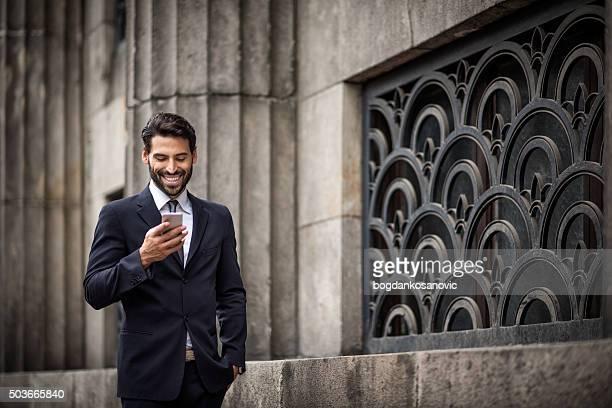 Geschäftsmann zu Fuß und SMS-Nachrichten
