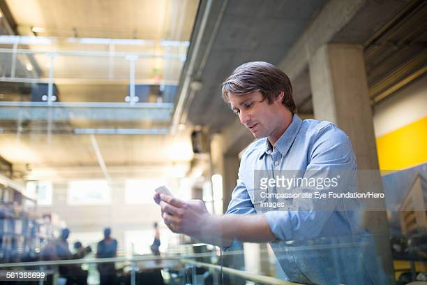 Businessman texting mobile phone in modern office
