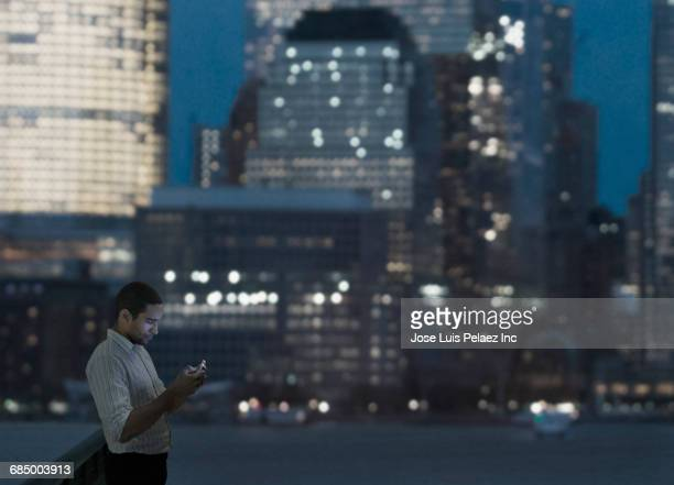 businessman texting on cell phone in city at night - città di west new york new jersey foto e immagini stock