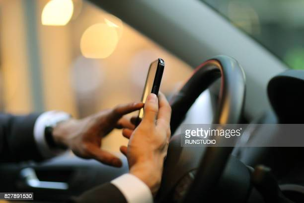 Businessman texting on his smart phone while driving a car