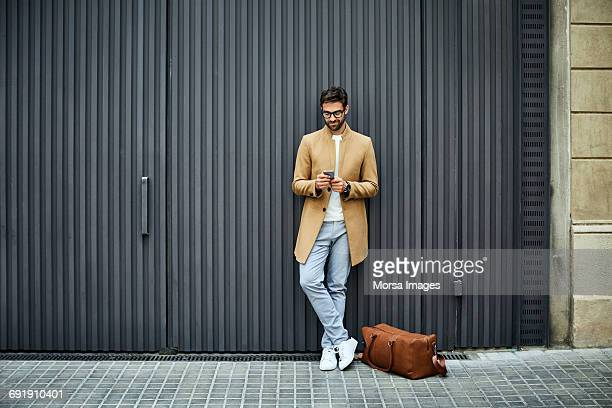 Businessman texting on mobile phone against wall