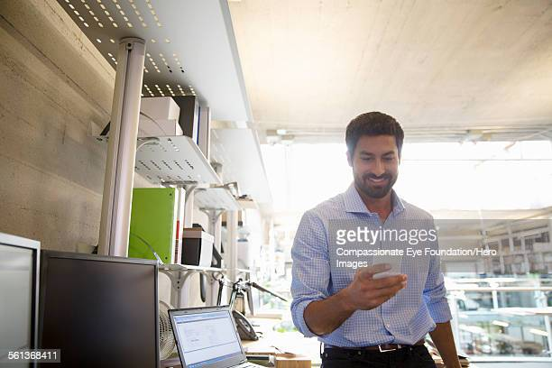 Businessman texting on mobile phone in office