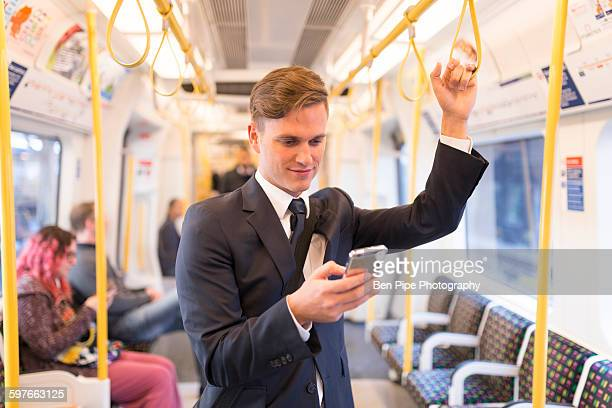 Businessman texting on tube, London Underground, UK