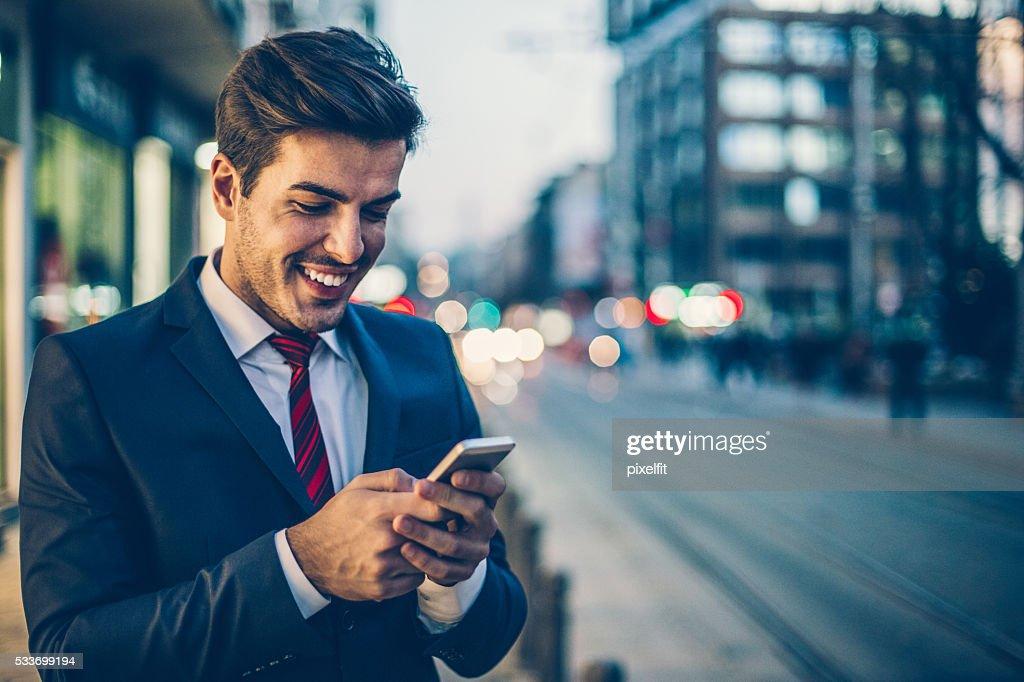 SMS uomo d'affari all'aperto di sera : Foto stock