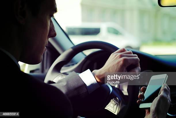 Homme d'affaires à envoyer des SMS, conduire une voiture