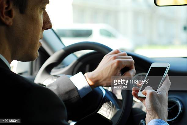Businessman texting while driving a car