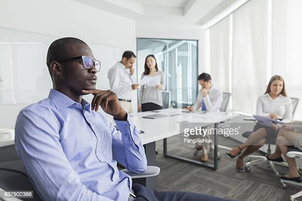businessman thinking during meeting in office - verlegen stockfoto's en -beelden