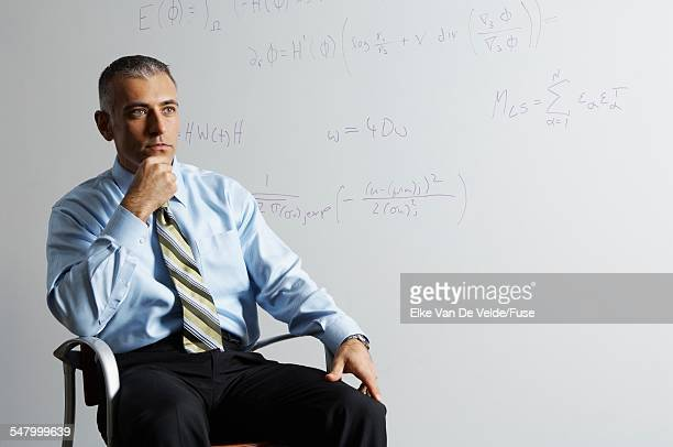 Businessman Thinking next to Whiteboard
