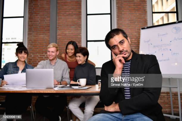 businessman thinking while colleagues discussing on laptop in background - cheek stock pictures, royalty-free photos & images