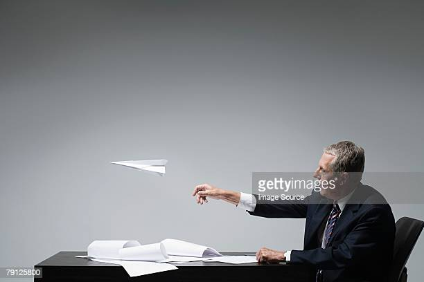 A businessman throwing a paper aeroplane
