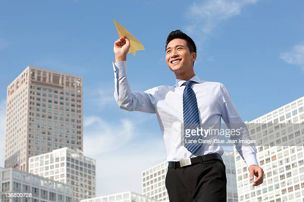 Businessman Throwing a Paper Airplane