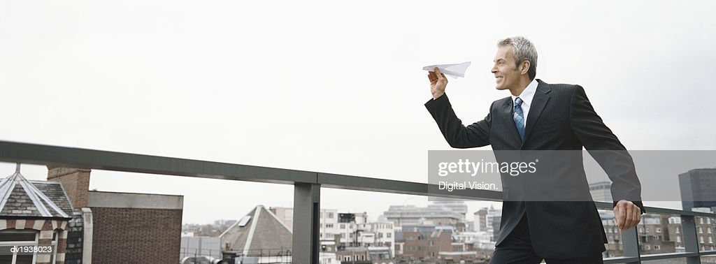Businessman Throwing a Paper Plane From the Rooftop of a Building : Stock Photo