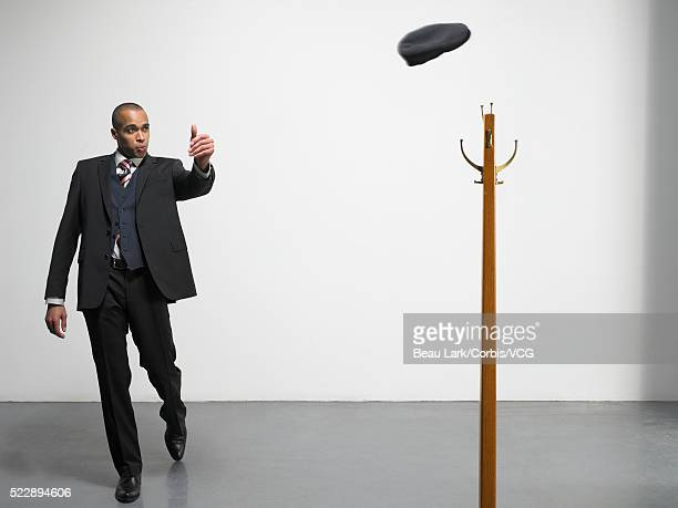 Businessman throwing hat onto coat rack