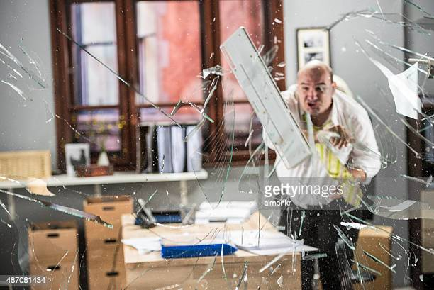 Businessman throwing keyboard on glass