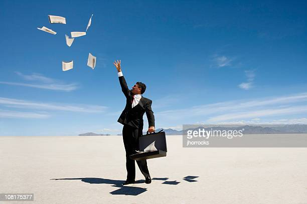 Businessman Throwing papers in wind