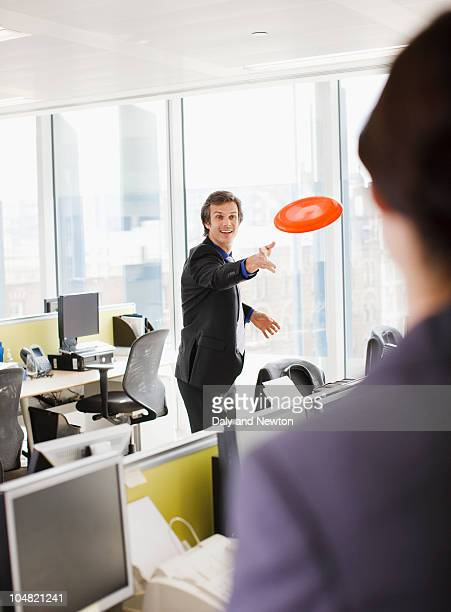 Businessman throwing plastic disc in office
