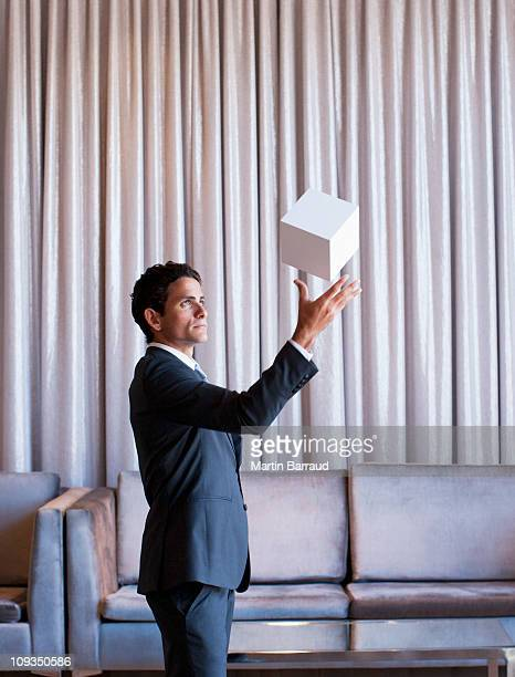 Businessman throwing white cube in the air