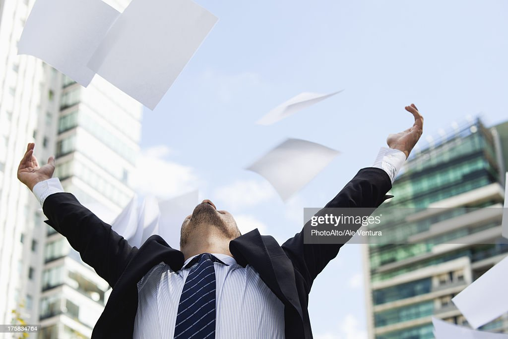 Businessman thrwoing paper in air : Stock Photo