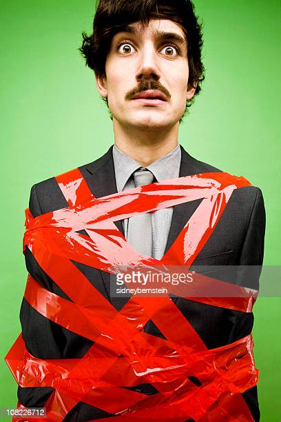 businessman tied up in red tape - bureaucracy stock pictures, royalty-free photos & images