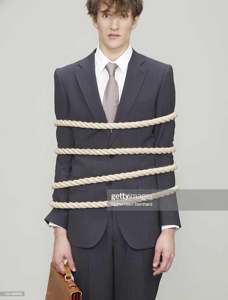 businessman tied up with rope looking shocked : Stock Photo