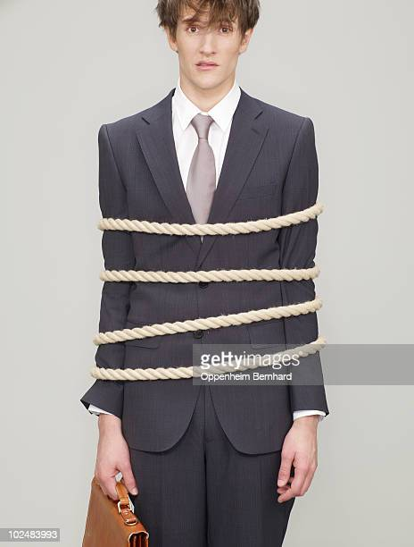 businessman tied up with rope looking shocked