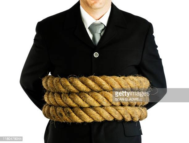 businessman tied with rope - restraining stock pictures, royalty-free photos & images