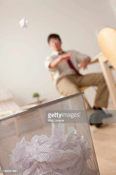 Businessman tossing ball of paper into wastebasket