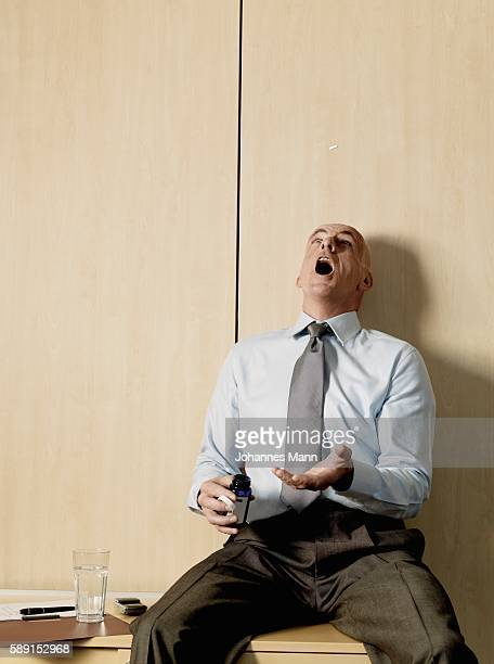 Businessman tossing pill in air