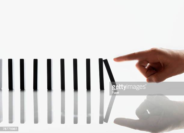 Businessman Touching Domino Pieces Arranged in a Line