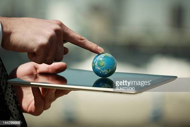businessman touching globe ball on the tablet PC