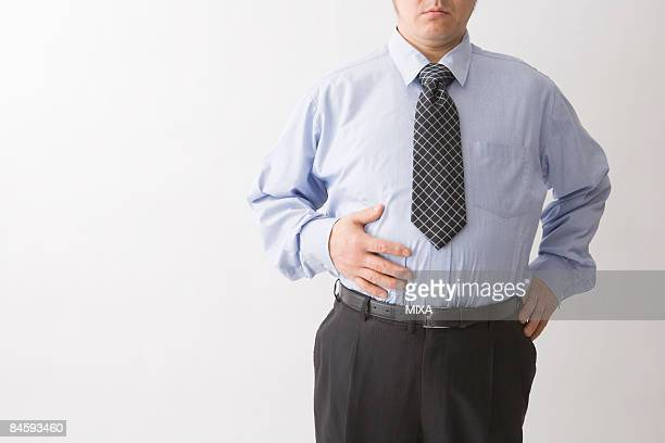Businessman touching his belly