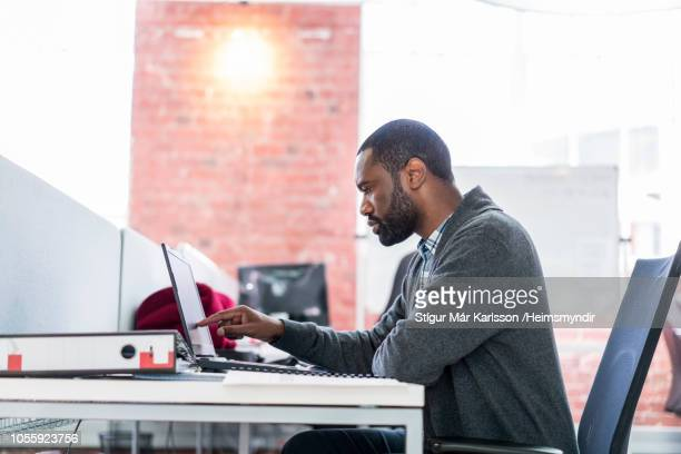 Businessman touching laptop at desk in office