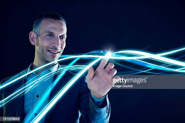 businessman touching lines of light - data stream stock photos and pictures