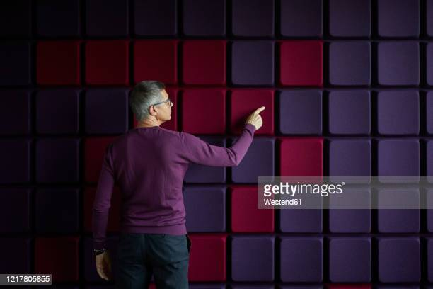 businessman touching noise reduction wall in office - toucher photos et images de collection