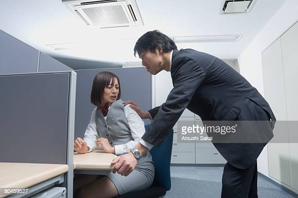 Businessman touching office worker's shoulder