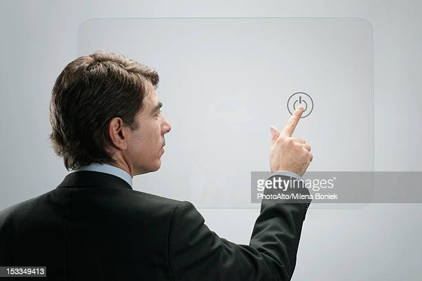 Businessman touching power button on advanced touch screen interface