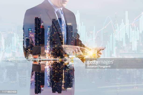 businessman touching smart phone in hand working abstract business chart bars on bright city background. trade concept. double exposure - börsenhändler stock-fotos und bilder