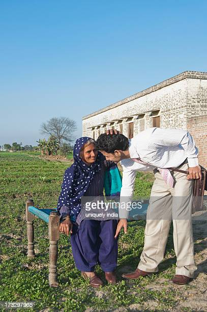 Businessman touching the feet of his mother in the field, Sonipat, Haryana, India