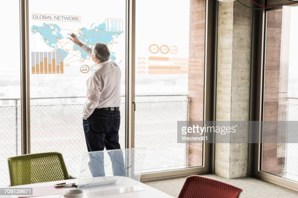 Businessman touching windowpane with world map and global network in office